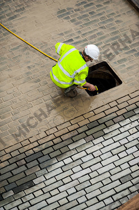 bgn-wed 312 d491   Drain cleaning and path laying   Keywords: hardhat, building, public works, drain, drains, manhole, hi vis, hose, block paving, cementing, grouting, wet, mortar, stone, water, spray, clean, path, pavement, sidewalk, preparation