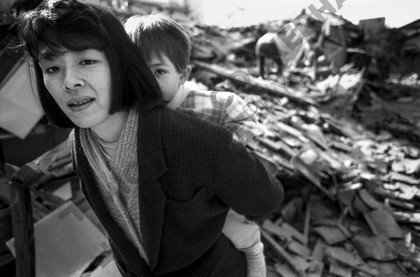mhc-ghe 195 b1-29   Fumi Okamoto and her daughter, Hana, survived the collapse of their house (in the background).   Keywords: kobe, earthquake, house collapse, japan, mother, daughter, child, hug, protect