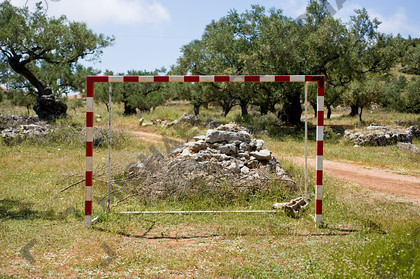 mhc-zky 508 d281   Empty goal, Zakynthos   Keywords: goal, aim, target, game, football, beautiful game, hazard, red and white, stripes, net, rubble, greece, zante, zakynthos, olive grove, lazy summer, green, dry, earth, on target, missed target, opportunity, opportunities, empty, boys, play
