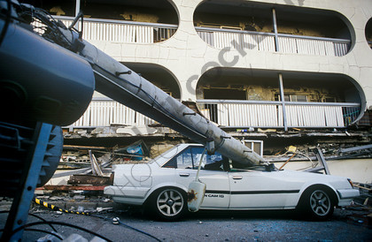 mhc-ghe 195 s4-24   A building and car are both flattened by the magnitude 7.3 earthquake.   Keywords: kobe, earthquake, destruction, japan, car, building, crushed, crush, telegraph pole