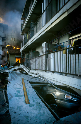 mhc-ghe 195 s3-21   Large apartment blocks collapse on themselves. Often they were built above their own carports which took the brunt of the damage   Keywords: destruction, kobe, earthquake, japan, fire, car, crush