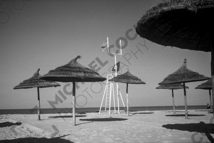 mhc-tun 401 s006   Deserted beach, Hammamet, Tunisia   Keywords: Tunisia, beach, deserted, Hammamet, shade, lifeguard tower, flag, sand, black and white, lonely, isolation
