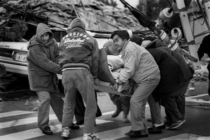 mhc-ghe 195 b3-18   When survivors were pulled out of the rubble people had to create makeshift stretchers and carry them to first aid stations which had been set up in sports fields and school playgrounds.   Keywords: survivor, rubble, help, stretcher, medical attention, rush, rubble, power cables, men, earthquake, kobe, japan