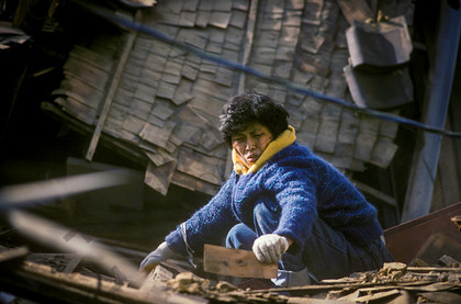 mhc-ghe 195 s2-18   A woman digs through the remains of her house trying salvage whatever she can, but is grateful to be alive.   Keywords: destruction, kobe, earthquake, japan, woman, salvage, dig, house