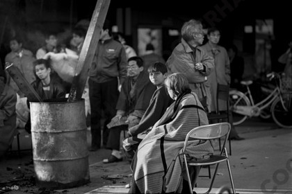 mhc-ghe 195 b3-17   People made homeless by the quake gathered around braziers with only rugs to keep them warm, while the waited for news and help from the authorities. The wait was frequently a long one.   Keywords: Woman, boy, men, brazier, warm, cold, huddle, wait, earthquake, kobe, japan