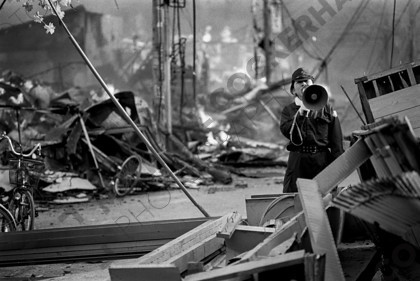 mhc-ghe 195 b3-15   The emergency services were stretched to the limits trying to protect and inform the public.   Keywords: policewoman, megaphone, disaster zone, earthquake, japan, kobe, fire, destruction