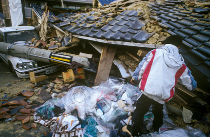 mhc-ghe 195 s4-22   In some places children were left to fend for themselves, trying to recover things from their destryed homes   Keywords: destruction, kobe, earthquake, japan, roof, tiles, boy, alone